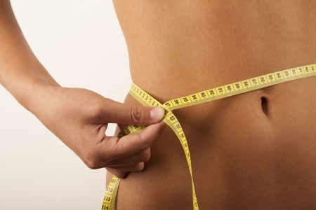Woman measuring her waist Stock Photo