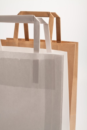 consumerism: Paper bags on white background. Consumerism symbol.