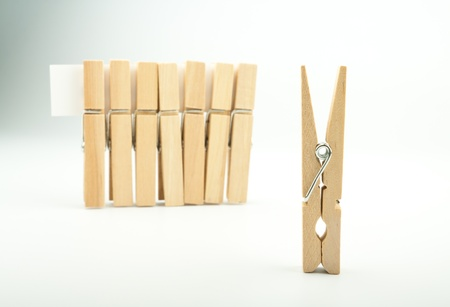 Wooden clothes pegs on light background Stock Photo - 17334867