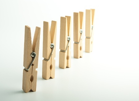 detach: Wooden clothes pegs on light background Stock Photo