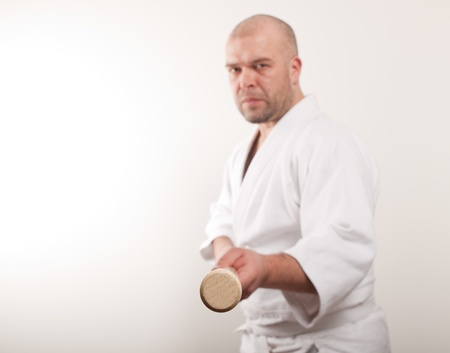 Aikido man with a stick on a light background Stock Photo - 17488275