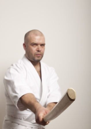 Aikido man with bokken on a light background Stock Photo - 17488277