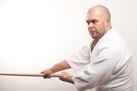 Aikido man with bokken on a light background photo
