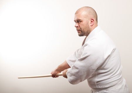 Aikido man with bokken on a light background Stock Photo - 17488278