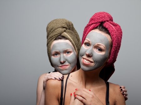 Clay facial mask. Two happy sisters