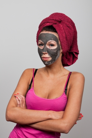 mud woman: Clay facial mask. The portrait of young woman.