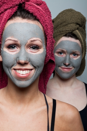 spa mud: Clay facial mask. Two happy sisters