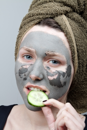 The portrait of young woman with Clay facial mask photo