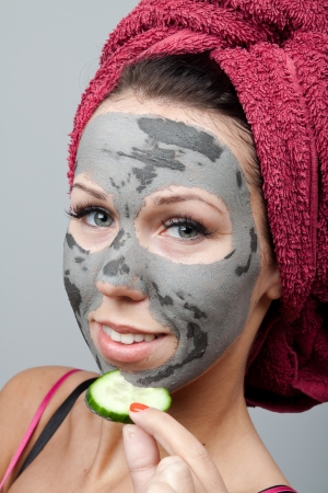 Clay facial mask. The portrait of young woman. photo