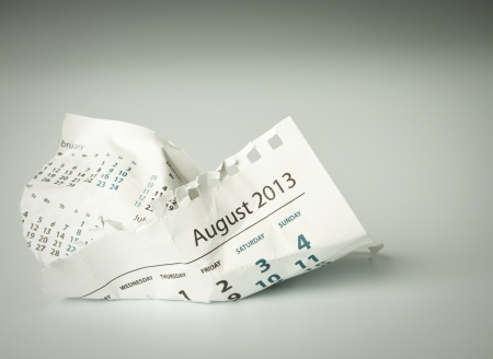 August. Calendar sheet. Crumpled paper on the floor. photo