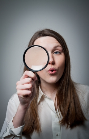 Young woman looking through loupe photo