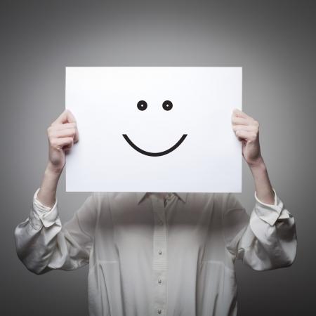 Jeune femme se cachant son visage avec un papier blanc avec un visage souriant là-dessus Banque d'images