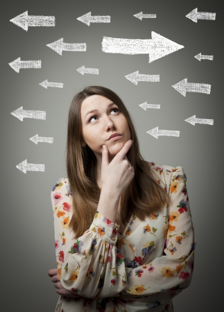 hesitation: Uncertain girl is looking at arrows. Girl full of doubts and hesitation. Stock Photo