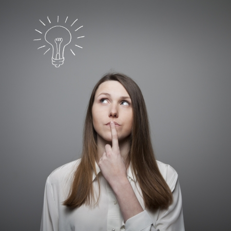 unintelligent: Young woman having an idea with light bulb over her head