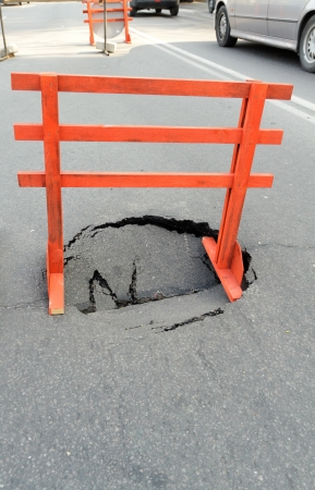 warning sign and a hole on the road photo