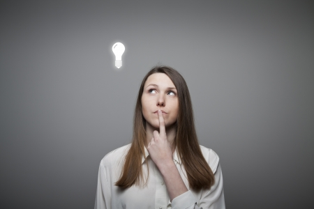 unintelligent: Young woman having an idea with light bulb over her head.