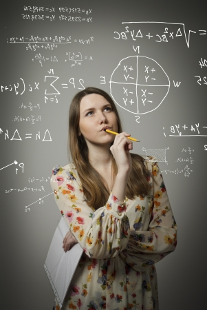 Thoughtful girl holding pen and documents and solving equation. photo