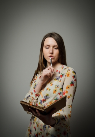 Thoughtful girl holding pen and diary photo