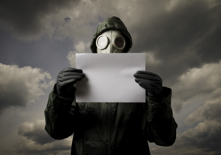 Man wearing a gas mask on his face and holding white paper Imagens
