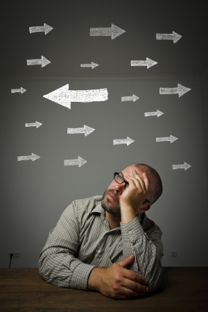 uncertain: Man in thoughts  Uncertain man is looking at arrows  Man full of doubts and hesitation