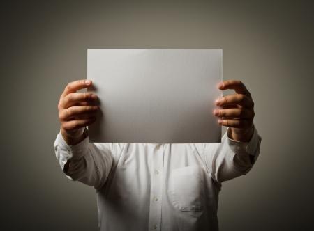 Hombre que sostiene el papel blanco en sus manos.