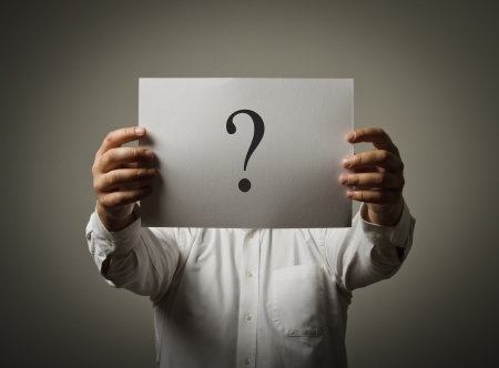 point of demand: Man holding white paper with question-mark. Man having no answers to a question.