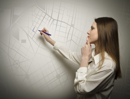 Young woman drawing a route on the city map photo
