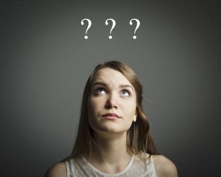 esitazione: Ragazza in bianco pieno di dubbi e esitazioni Ragazza e tre punti interrogativi sopra la sua testa