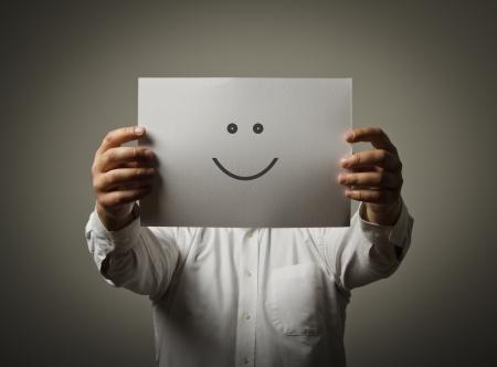 semblance: Uomo che nasconde il suo volto dietro un libro bianco con una faccina sorridente su di esso
