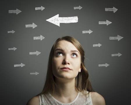 doubting: Uncertain girl is looking at arrows  Girl in white full of doubts and hesitation  Stock Photo