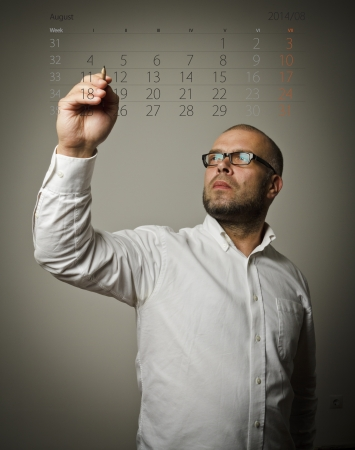 Man in white is writing on a August calendar  Time is passing   photo