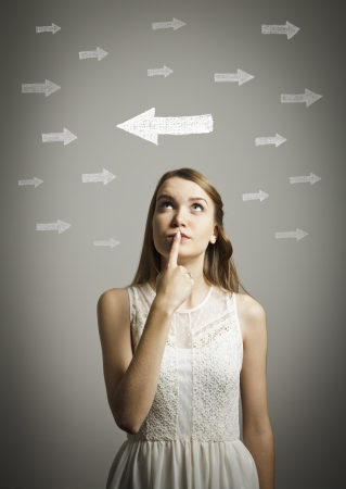 Uncertain girl is looking at arrows  Girl in white full of doubts and hesitation  Stock Photo