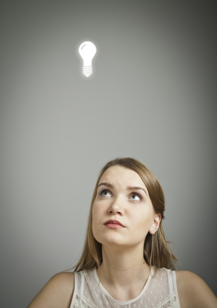 unintelligent: Girl in white having an idea with light bulb over her head