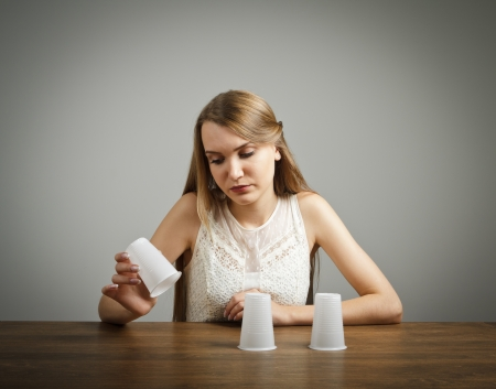 incertitude: Girl in white is trying to guess what is under the cups  Stock Photo