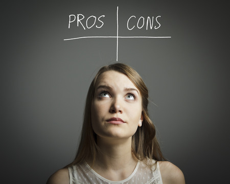 Girl in white is thinking  Pros and cons concept Imagens - 27749678