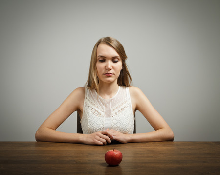 Girl in white sitting in front of an apple photo