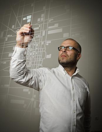 creador: Hombre en blanco dibujo de una ruta en el mapa de la ciudad. Foto de archivo