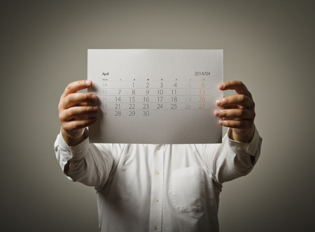 Man holding April calendar list in his hands. photo