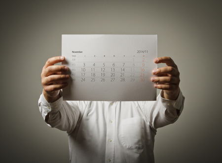 Man holding November calendar list in his hands. photo