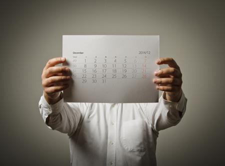 Man holding December calendar list in his hands. photo