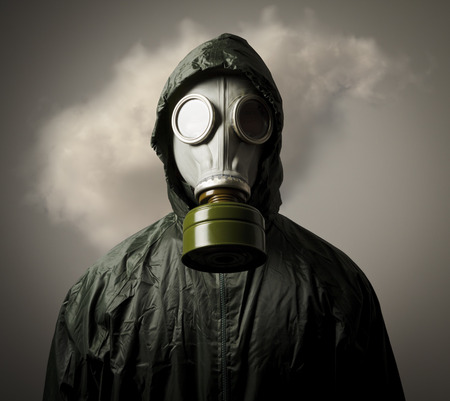 Man wearing a gas mask on his face and a cloud behind his back.