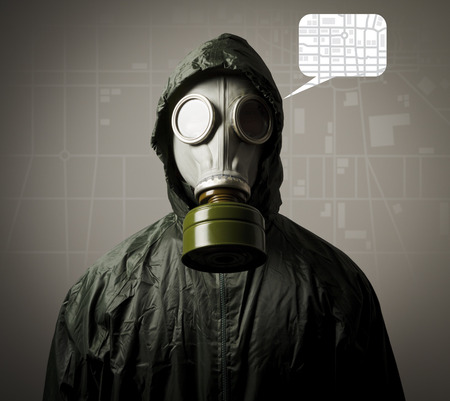 Man wearing a gas mask on his face and a city map behind his back  Evacuation concept  photo
