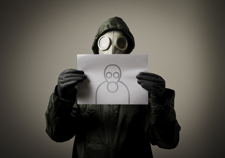 Man wearing a gas mask on his face and holding self-portrait  Self-portrait concept  photo