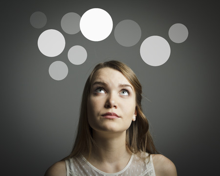 Girl in white having an idea with gray bubbles over her head  Imagens