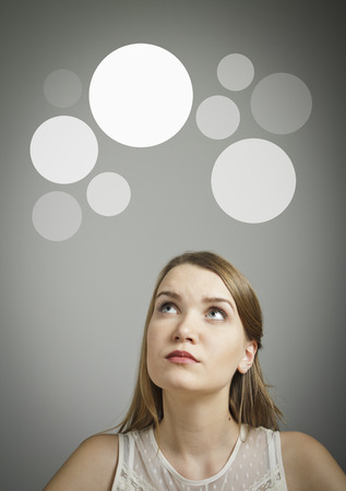 Girl in white having an idea with gray bubbles over her head  Stock Photo