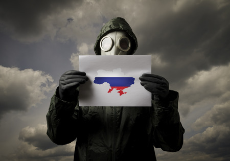 annexation: Man wearing a gas mask on his face and holding white paper and Ukraine map with Russian flag.