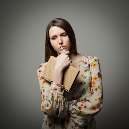 indecision: Thoughtful girl holding pen and diary Stock Photo