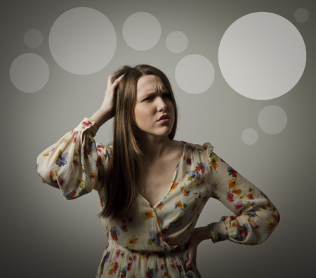 forgetfulness: Girl is trying to remember something  Forgetfulness concept  Grey bubbles in the background  Stock Photo