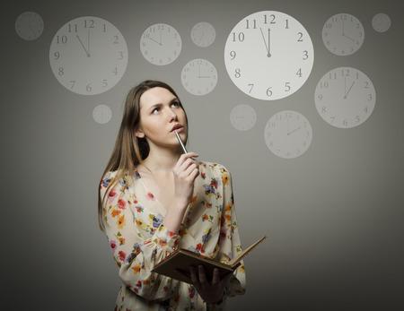 Muchacha pensativa que sostiene la pluma y el cuaderno Tiempo concepto