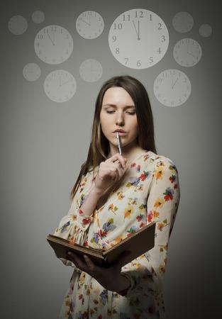 펜 및 노트북의 시간 개념을 잡고 사려 깊은 여자